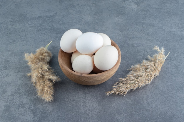 Organic raw eggs in wooden bowl.