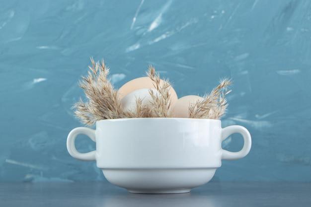 Uova crude organiche in ciotola di legno.