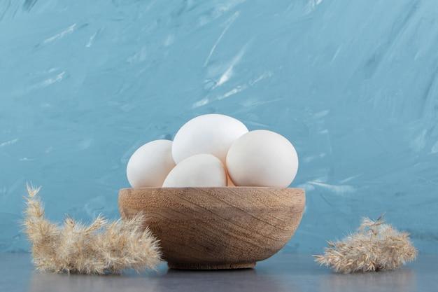 Uova crude biologiche in ciotola di legno