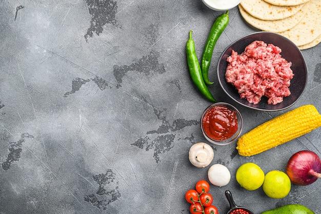 灰色のテクスチャ背景、上面図の上に、黒いボウルに材料を入れた野菜のクシンを添えたメキシコのタコス用の有機生ひき肉。