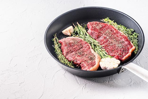 Органические сырые стейки из говядины пиканья на черной тарелке