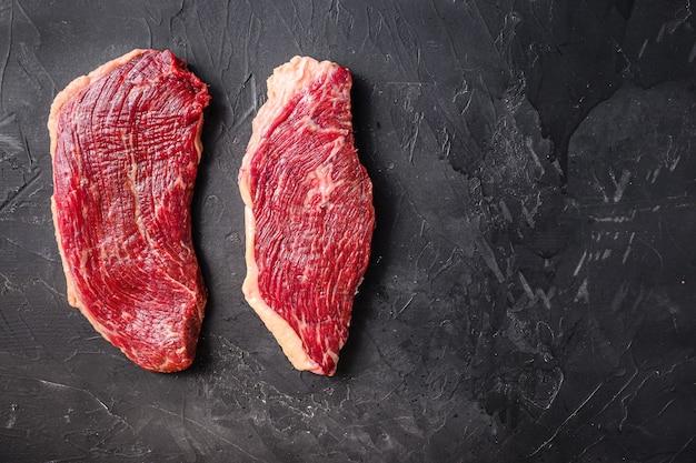 검은색 질감의 배경 위에 있는 유기농 생 피칸하 쇠고기 스테이크, 텍스트를 위한 공간이 있는 위쪽 전망.