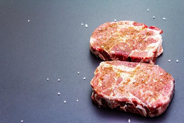 Organic raw pork steak, marinated in dry spices, with sea salt
