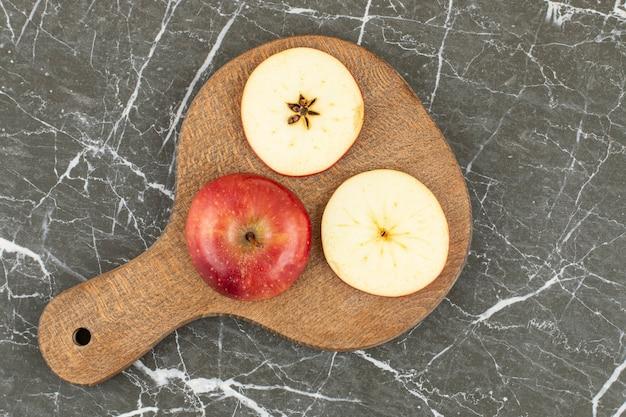 有機赤いリンゴ。全体と木の板にスライス。