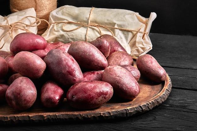 木製のテーブルのエコロジカルパッケージ、製品の配達の古いボードの有機赤いジャガイモの皮。