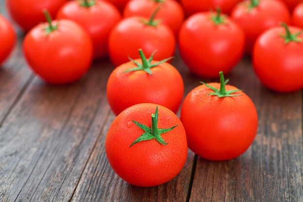 유기농 빨간 토마토와 물은 나무 테이블에 떨어집니다.
