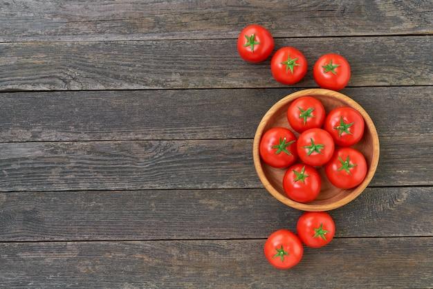 텍스트 복사 공간이 있는 소박한 나무 테이블에 있는 나무 그릇에 유기농 빨간 토마토.