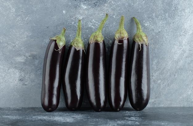 Fila di melanzane mature organiche su sfondo grigio.