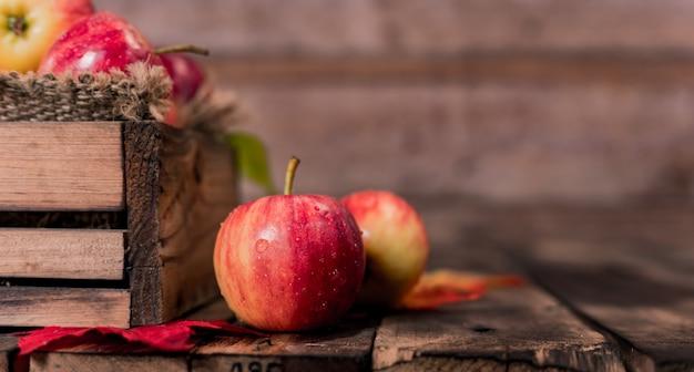 Органические спелые красные яблоки в деревянной коробке. падение урожая рог изобилия в осенний сезон. свежие фрукты с предпосылкой деревянного стола.