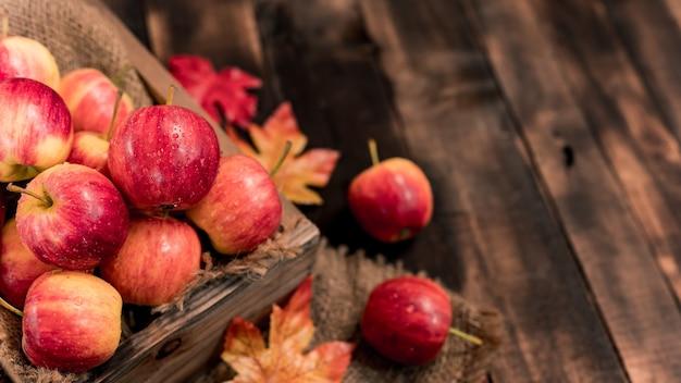 木製の箱に有機熟した赤いリンゴ。秋の季節の秋の収穫の宝庫。木製のテーブルの背景を持つ新鮮な果物。