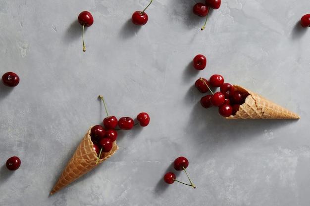 Органические спелые красные фрукты вишня и вафельные чашки для домашних десертов на сером каменном фоне с местом для текста. летние органические сырые продукты.