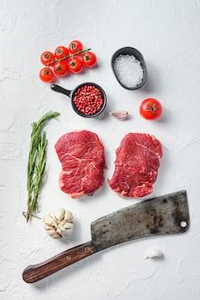 유기농 럼프 스테이크, 조미료를 곁들인 생 소고기, 로즈마리, 마늘, 정육점 칼.