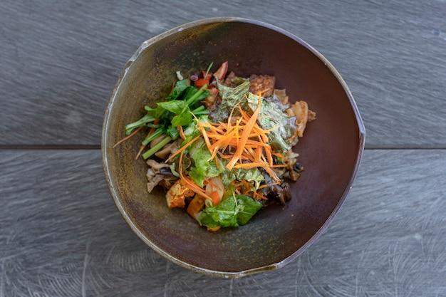 グリーンカレーライス、なす、キムチ、野菜の煮込み、きのこ、テンペベーコン、豆腐のオーガニックサラダを粘土のボウルに入れて提供しています。閉じる。健康的な食事の概念。