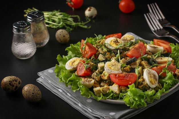 鶏肉、チェリートマト、ウズラの卵、ブラックオリーブ、マイクログリーンを使ったオーガニックサラダを暗い表面に、健康的な食事の日に