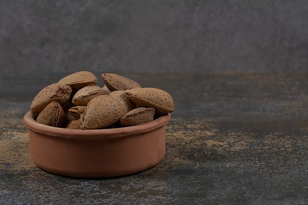 Organic shelled almonds in ceramic bowl.