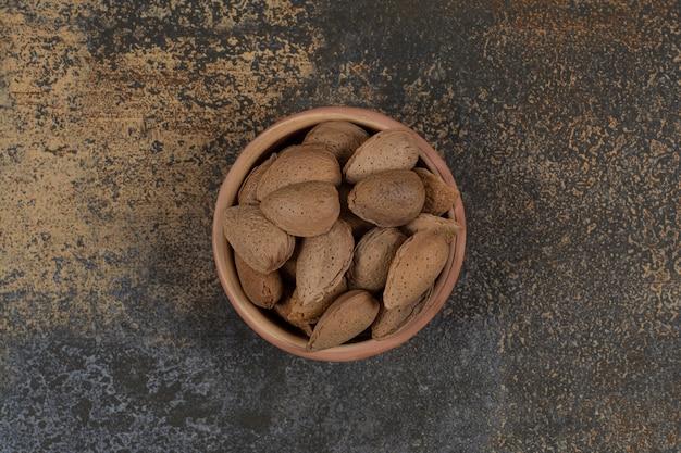 Organic shelled almonds in ceramic bowl.
