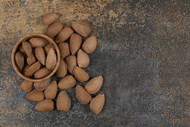 Organic shelled almonds in wooden bowl.