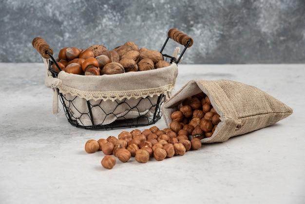 穀粒の荒布を入れたバスケットに入った有機殻のヘーゼルナッツとクルミ。