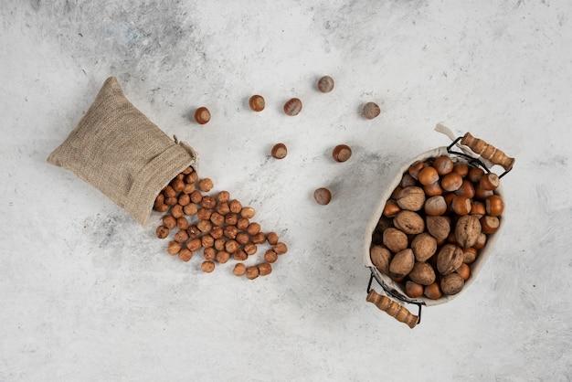 Cestino biologico di nocciole e noci sgusciate con sacco di gherigli.
