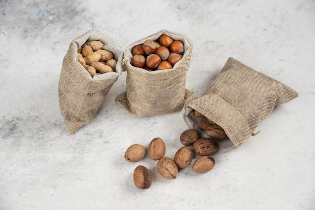 Nocciole sgusciate organiche, arachidi e noci in tela di sacco su tavola di marmo.