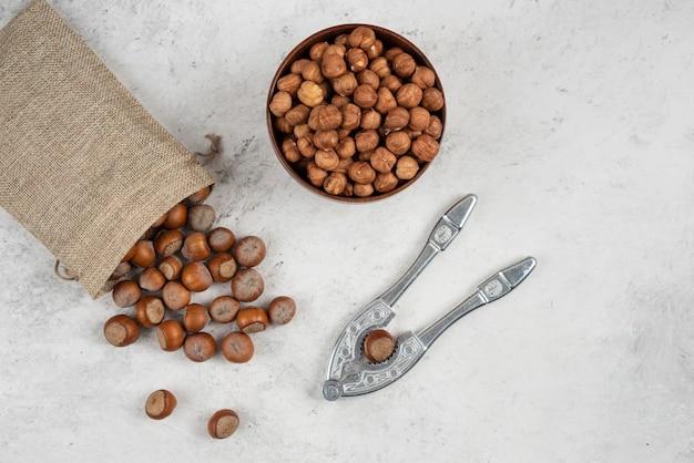 Nocciole sgusciate e gherigli organiche in tela con attrezzo per cracking.