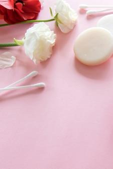 분홍색 배경에 유기농 스킨 케어 제품과 섬세한 꽃. 건강한 화장품 . 웰빙 뷰티 트리트먼트.