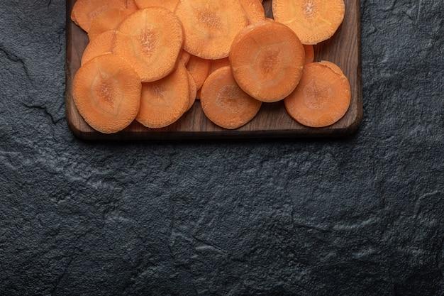 Carote affettate organiche sulla tavola di legno. foto di alta qualità