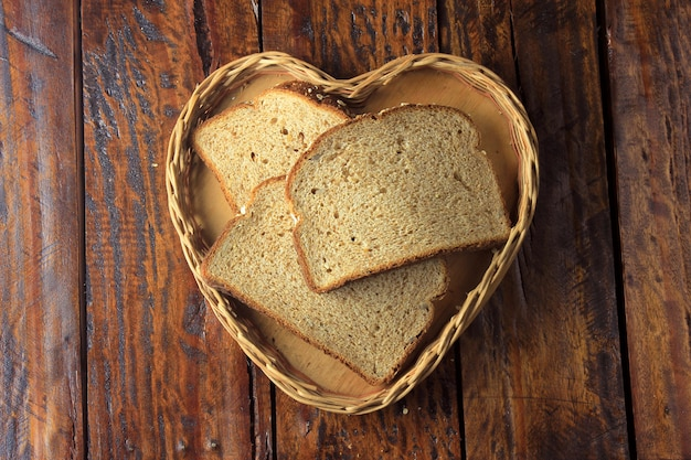 Organic sliced wholemeal bread inside shape heart basket