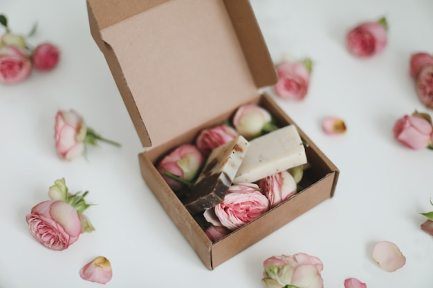 Organic soap bars in a craft gift box with flowers on a floral surface top view