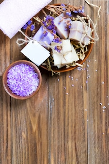 Organic soap in a basket with dry flowers and natural sea salt in a bowl on a brown wooden table with copy space.