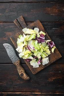 有機春ミックスレタスセット、木製まな板、古い暗い木製のテーブル、上面図フラットレイ