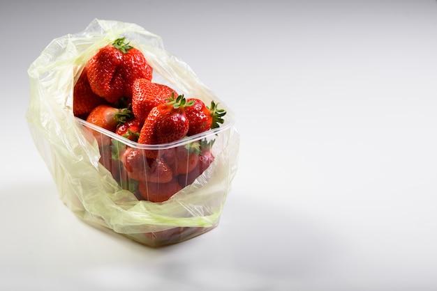 Органическая клубника в пластиковой коробке и сумке.