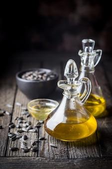 暗い木製の背景にヒマワリの種と小さなガラスの瓶に有機ひまわり油