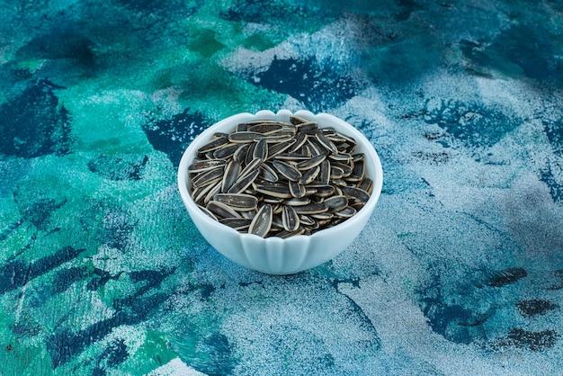 Semi di girasole organici in una ciotola, sul tavolo blu.