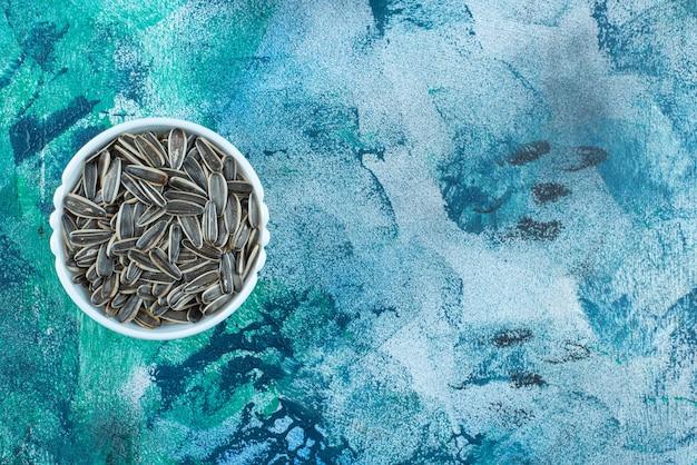 青のボウルに有機ヒマワリの種。