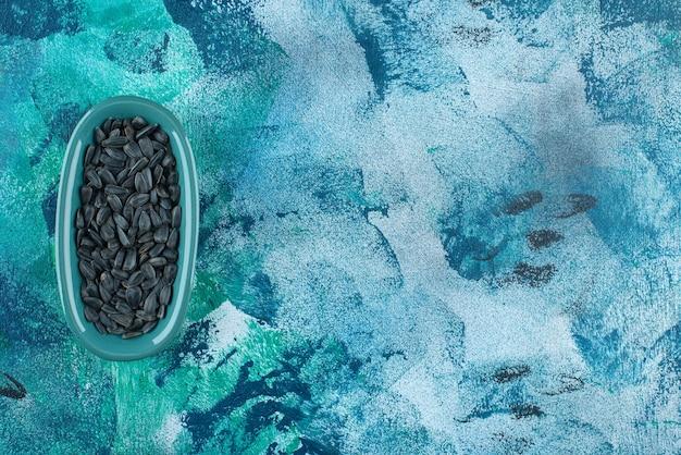 Semi di girasole organici in un piatto, sulla tavola blu.
