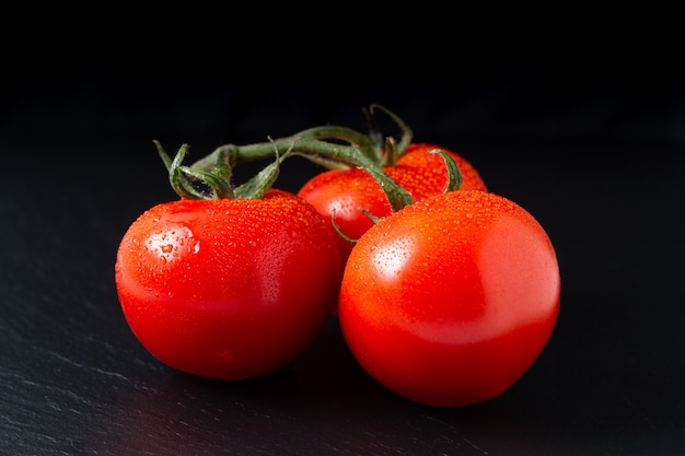 Organic tomatoes on black slate board with copy space