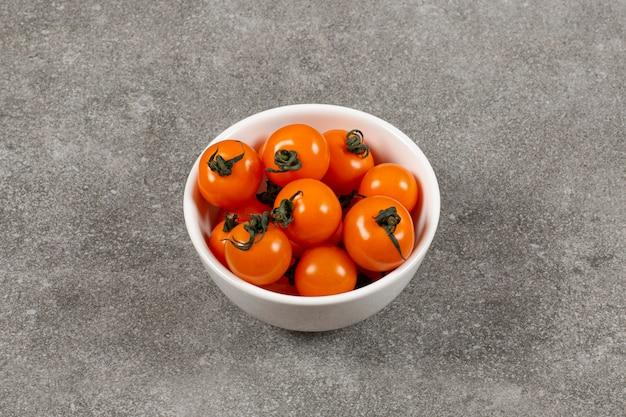 Pomodori biologici nella ciotola, sul marmo.