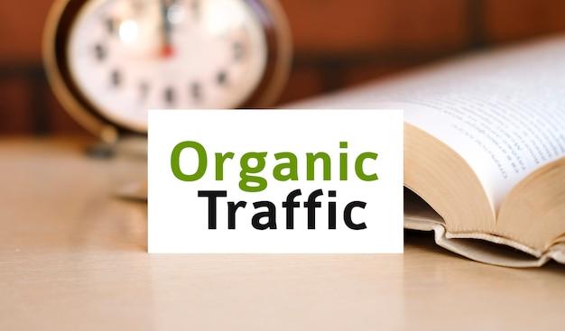 オーガニックトラフィック-白いノートと砂時計の時計、花の緑の葉のビジネスコンセプトテキスト