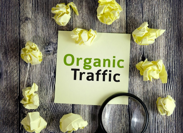 Organic traffic seo concept - text on yellow note sheets on a dark wooden background with crumpled sheets and a magnifying glass