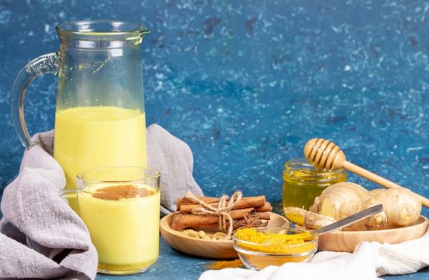 有機ターメリックミルク。ガラスと黄金のミルク、食材、青の背景に蜂蜜とデカンターの組成物。