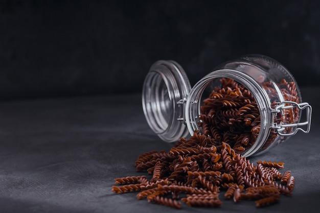 Органические сырые макароны гречихи fusilli в стеклянной банке на темном фоне. цельнозерновая лапша без глютена. концепция здорового питания.