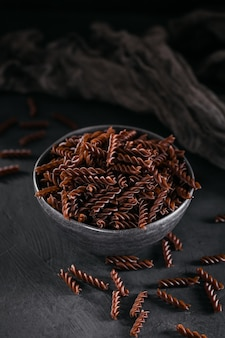 어두운 표면에 유기농 생 쌀된 메밀 fusilli 파스타. 통 곡물 글루텐 프리 국수. 건강 식품 개념.