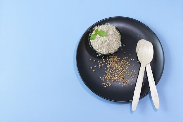 그릇 파란색 배경에 접시에 메밀 가루에 유기농 생 메밀 곡물 건강 개념