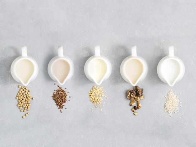 Органическое молоко vegan от сои, овсяной каши, риса, гаек, гречихи в кувшине молока на серой предпосылке. принципиальная схема диеты взгляд сверху.