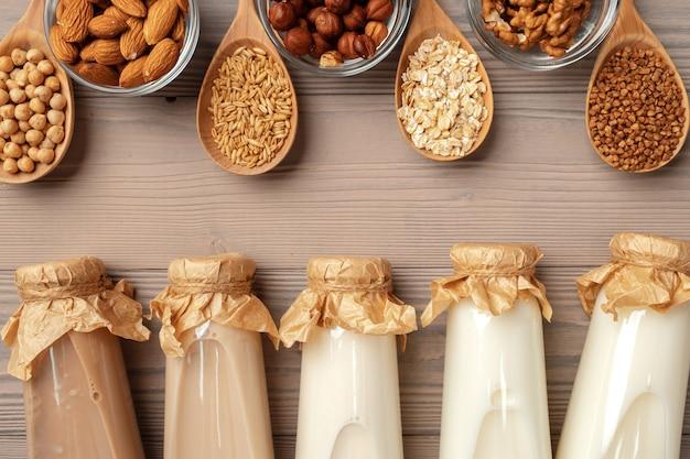 ガラスの牛乳瓶と木製の背景にバルク製品と有機ビーガン非乳製品牛乳