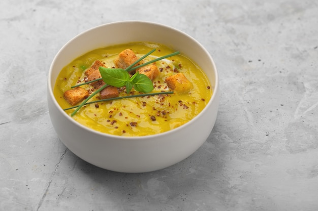 Organic vegetable puree soup with crackers, green onions and basil on a concrete background with copy space