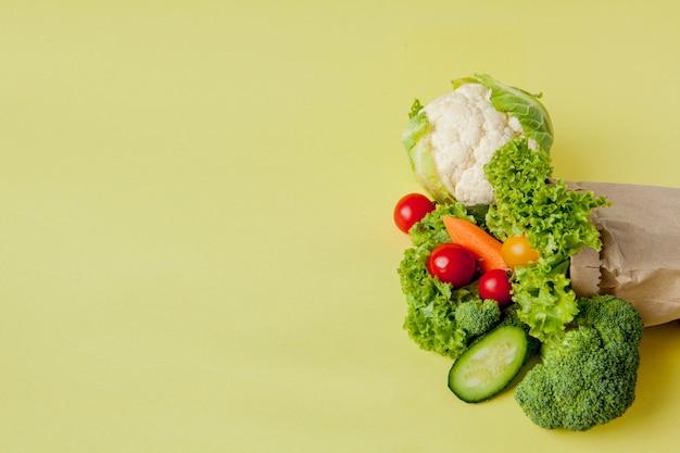 Organic vegetables broccoli cucumbers bell peppers apples in brown paper kraft grocery bag. healthy diet dietary fiber vegan
