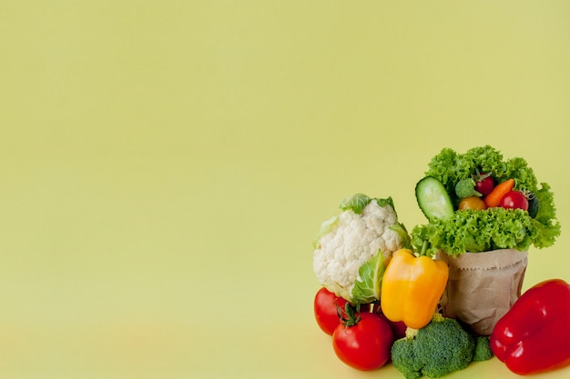 Organic vegetables broccoli cucumbers bell peppers apples in brown paper kraft grocery bag on yellow background. healthy diet dietary fiber vegan plastic free concept. poster banner