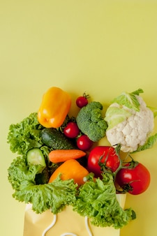 Organic vegetables broccoli cucumbers bell peppers apples in brown paper kraft grocery bag on yellow background